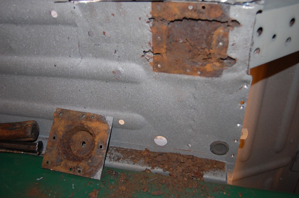 The enclosed area under the radius cups, on the other hand, often look like this.  What you are seeing here is the rusted away pieces of the floor panelm, which is sandwiched between the radius cup and the reinforcing plate on the top side.