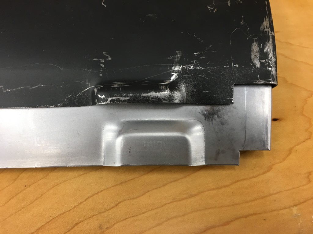 The Monocoque Metalworks sill - on the bottom of the photo in bare cold-rolled steel - has a rear drain hole that is EXACTLY like the factory sill. The competitor's rear drain hole is too shallow (and slightly too far forward...), and is usually completely sealed off once the sill is installed...